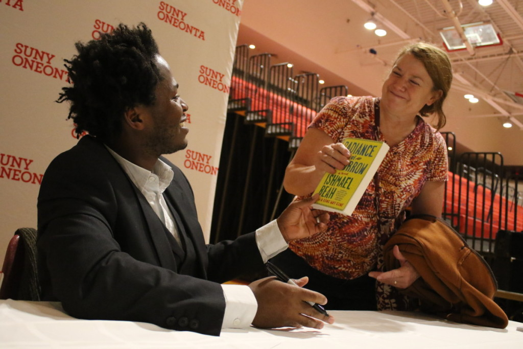 "Ishmael Baeh signs a copy of his memoir ""A Long Way Gone"" for Susan Ryder at the end of the annual Mills Lecture, held earlier this evening at SUNY Oneonta."