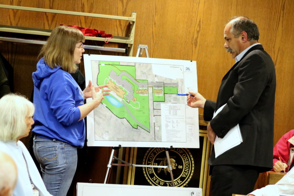 Oneonta Resident Kathy Hays and Steve Underhill, the development project manager for Housing Visions, square off in front of a map of the proposed Silver Creek project at the City Planning Meeting this evening. (Ian Austin/ AllOTEGO.com)