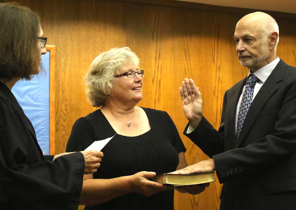 "A serious Gary Herzig, with his smiling wife Connie holding the Bible, is sworn in as mayor of Oneonta by City Judge Lucy Bernier. The ceremony, at about 6:40 p.m., may spell the end of 10 months of turmoil since the sudden passing of Mayor Dick Miller last Oct. 25. In remarks following the ceremony, the new mayor declared, ""the challenges are many, but there is reason for optimism."" And he ticked off a number of innovations. ""You know as well as I do that Oneonta is a special place. Together, we can make it an even better place. I promise to work with you on that."" (Jim Kevlin/AllOTSEGO.com)"