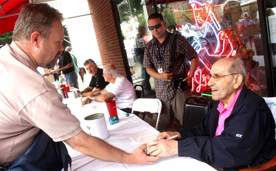 Yogi Berra was signing autographs in front of TJ's Place this afternoon as Induction Weekend got underway. Rolly Fingers is seated in the background. They were among dozens of MLB stars who will be autographing on Main Street through the weekend