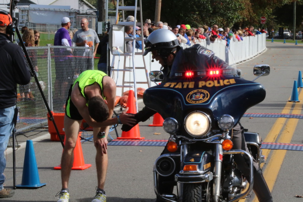 For the first time in several years, an Oneontan won the PIT Run 10K. Matthew Pohren, seen here moments after crossing the finish line with a time of 34:19, is congratulated by State Trooper Tim McQuaid, Binghamton, who was the pacer vehicle for the race. (Ian Austin/AllOTSEGO.com)