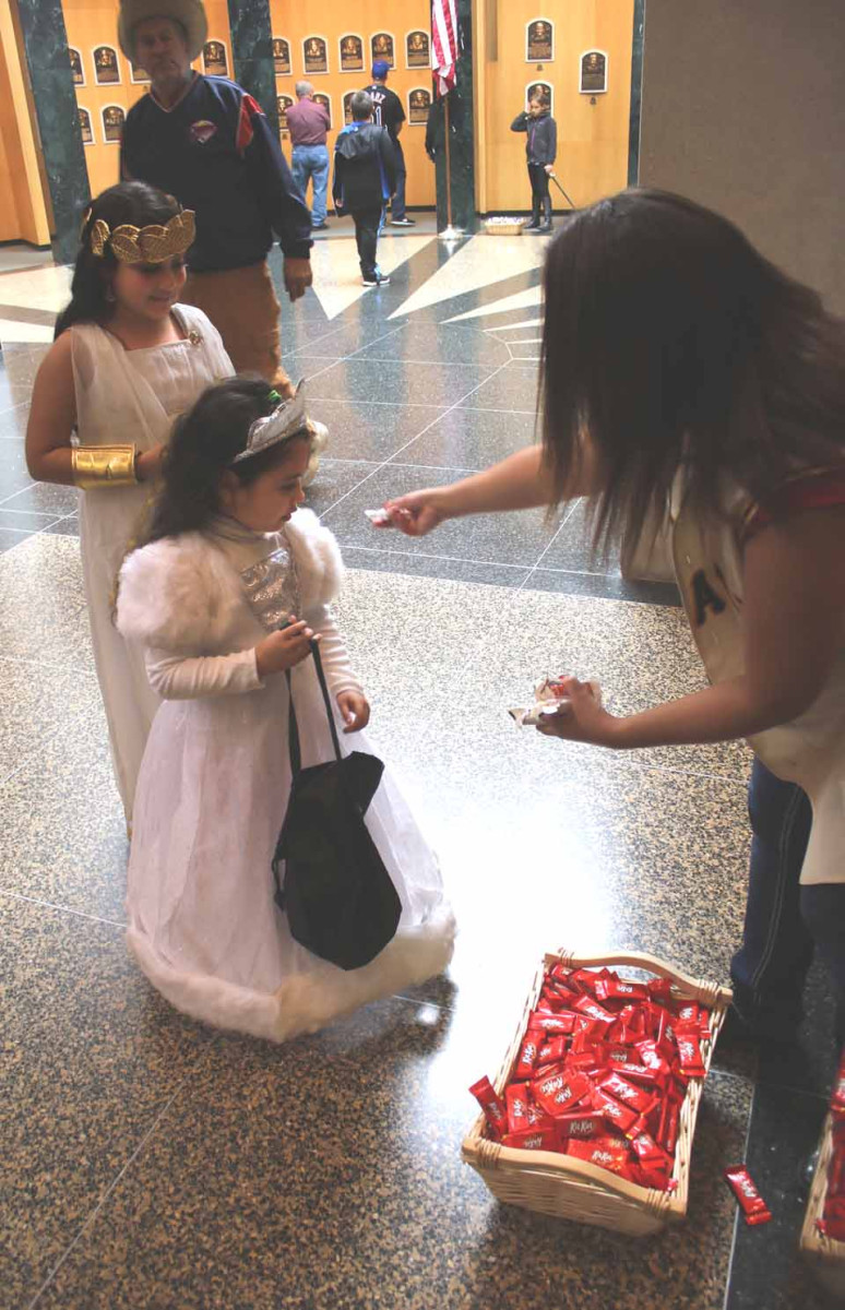 Just back at CCS after a year at the Singapore American School, Lily Shanker, 9, and her younger sister Siri, 5, partake of goodies being handed out in the Hall of Plaque by Felicia Eddy, a CGP second-year student from Smyrna, Chenango County. The Hall of Fame is handing out goodies until 5 p.m., when the Cooperstown Halloween Parade begins. (Jim Kevlin/AllOTSEGO.com)
