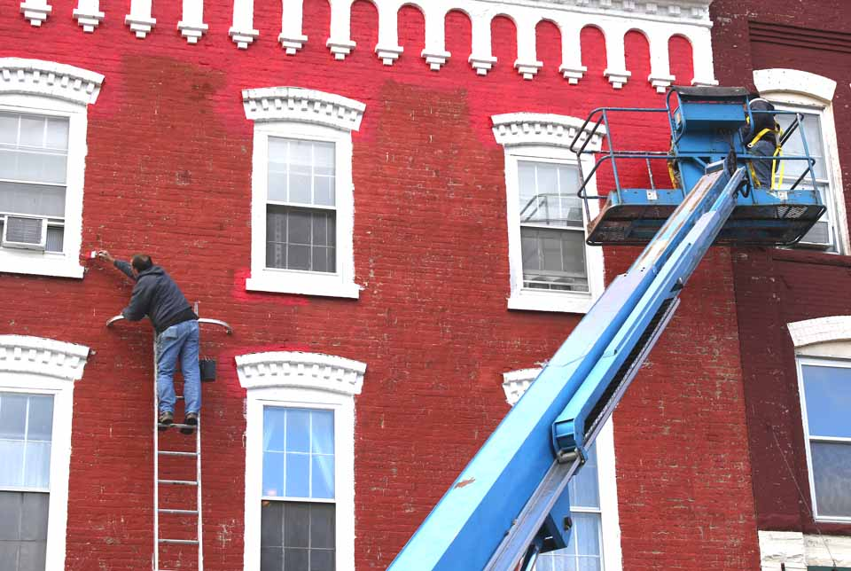 "The three-story former Sherry's Famous Restaurant brick block ""at the light"" in Cooperstown – now home to Mel's – is getting paint job. Steve Eldred, proprietor of Eldred Contractors, was on the job atop a ladder this morning. The building is owned by Fred and Karen Lemister; his parents were Sherry's proprietors. (Jim Kevln/AllOTSEGO.comO)"