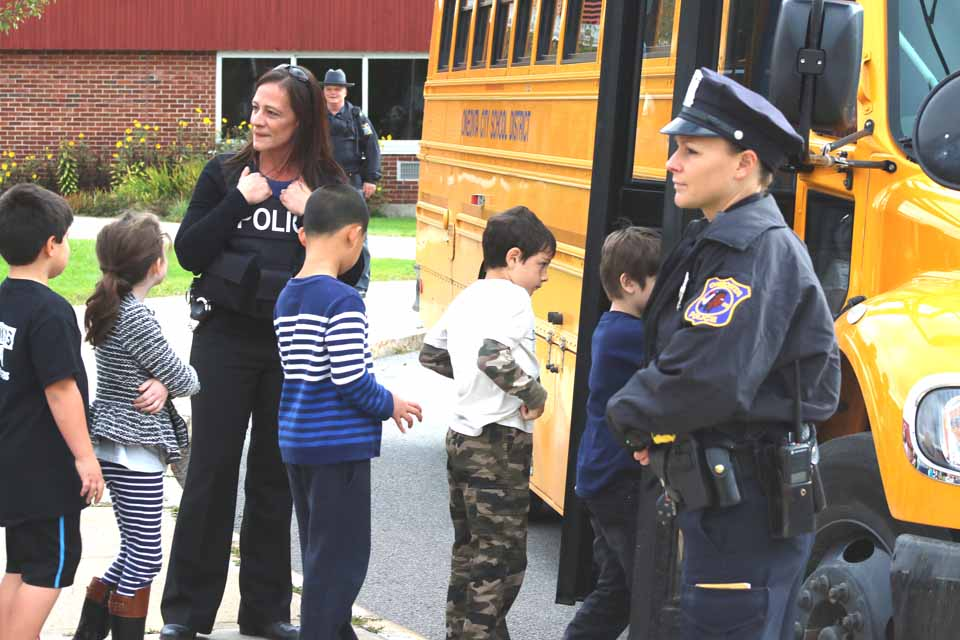 OPD Officer Kristen LaPointe, right, and Detective Jennifer Torres, center left, guide students on a school bus at Oneonta's Greater Plains Elementary School this morning during a police-training drill of procedures that would be followed in an emergency. (Ian Austin/AllOTSEGO.com)