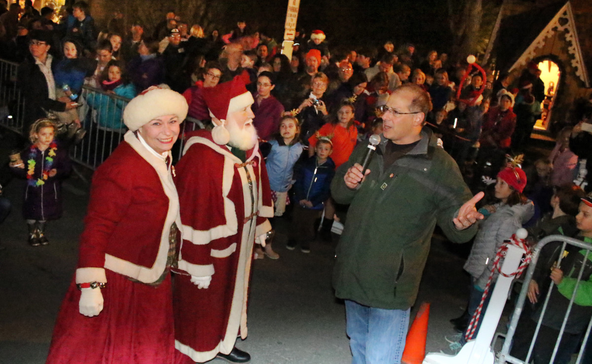 Cooperstown Mayor Jeff Katz, along with droves of families and onlookers, welcomed Santa Claus and Mrs. Claus to their cottage in Pioneer Park this evening. After a message of good tidings to the crowd, Father Christmas entered his cottage and began to see the first children of the season.  (Ian Austin/AllOTSEGO.com)