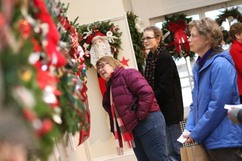 Abby Armstrong, Cooperstown native, inspects some of the many wreaths with sister-in-law Mary Armstrong and Barbara Rankin, Cooperstown, at the 15th annual Adorn-a-Door Festival, going on right now at the Cooperstown Art Association. Bidding goes until 4 p.m. (Ian Austin/AllOTSEGO.com)