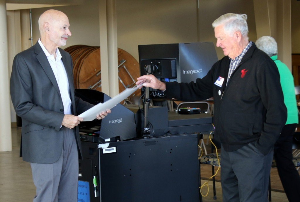 After casting his vote Mayor Gary Herzig hands his voting folder to election official Bob Hobkirk at the Foothills Preforming Arts Center. Polls opened at 6am this morning and by 9am had seen a nearly 200 voter turn out. Polls are open until 9pm tonight. (Ian Austin/ AllOTSEGO.com)