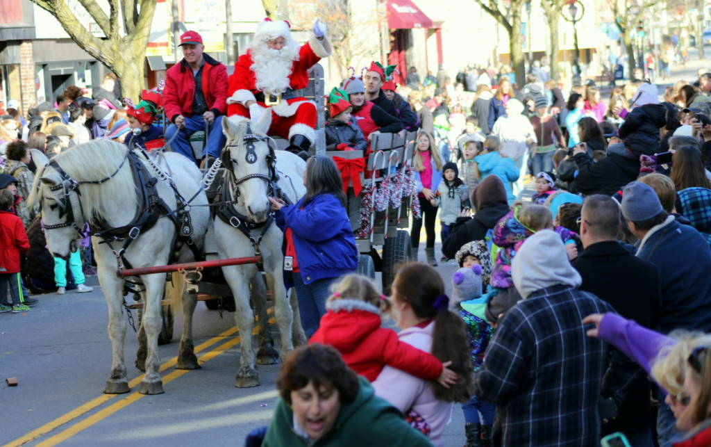 The streets were awash in holiday revelers welcoming Santa to Oneonta this afternoon, who sits atop his carriage, driven by Don Decker, Laurens, with his horses Maggie and Kate. (Ian Austin/ AllOTSEGO.com)