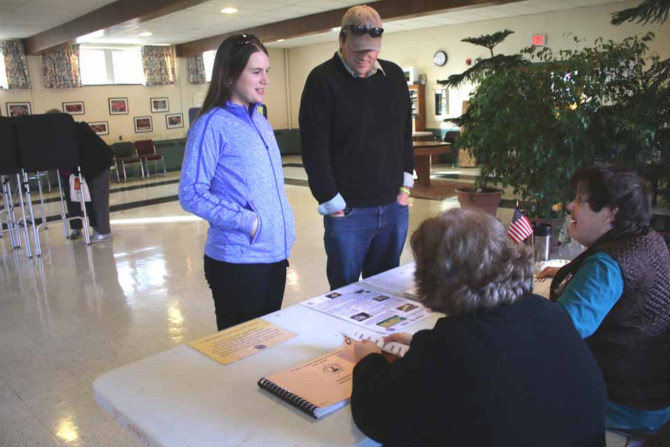 """Cooperstown Chamber of Commerce Executive Director Matt Hazzard and wife Stephanie answer election staffer Sue Straub's questions as they prepare to vote this morning at St. Mary's """"Our Lady of the Lake"""" parish hall in Cooperstown. Election official Rick Jagels reported turnout was """"steady."""" By 8:30 a.m., 82 people had voted. Polls are open around the county for town and county offices until 9 p.m. (Jim Kevlin/AllOTSEGO.com)"""