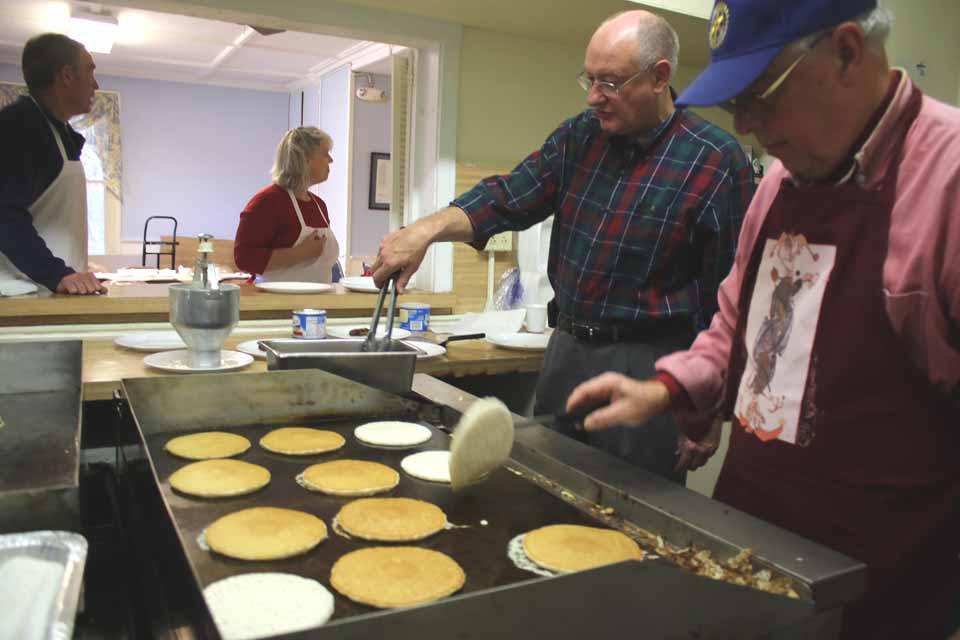 Cooperstown Rotarian Chuck flips pancakes at the club's traditional Election Day all-day flapjack fest the Veterans Club, 60 Main St. Martin Tillapaugh assists, which the Rev. Elsie Rhodes and Dave Bliss, unopposed candidate for county rep from the Middlefield-Roseboom-Cherry Valley district, wait to speed the breakfast to patrons. Pancake will be served until 2 p.m., then from 4 to 7 p.m. Also traditional, politicians gathered, including county Rep. Rick Hulse, R-Fly Creek, and his Democratic challenger, Andrew Marietta. (Jim Kevlin/AllOTSEGO.com)