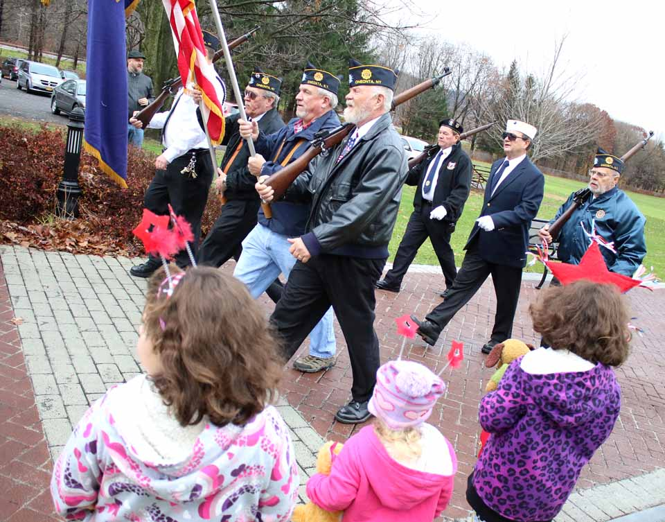 Oneonta's Three-D sisters, Delilah, Dahlia and Dannah Levinson, watch as the color guard, Gary Ballard (Navy), Bernie White (Air Force), Steve Fargo (Marines) and Jim Williams (Navy) march up Neahwa Park's Veterans Memorial Walkway Wednesday, Nov. 11, for Veterans' Day commemorations. The rifle detail is Tony Moore, Wayne Gregory and Harry Martin, behind. (Ian Austin/AllOTSEGO.com)