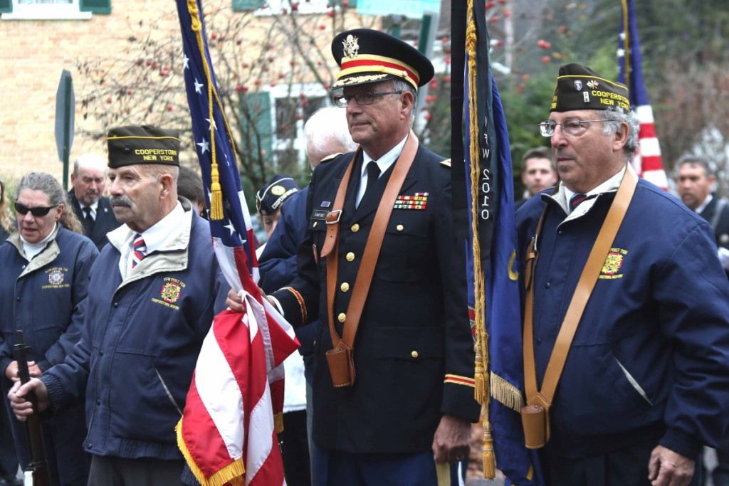 "The honor guard at this morning's Veterans' Day Parade in Cooperstown are, from left, Paul Elkins, David Sanford and Frank Capozza. The commemoration of soldiers' sacrifices, including a burning of used flags, took place at the village's ""doughboy"" statue at the foot of Pine Boulevard, across from The Otesaga. (Jim Kevlin/AllOTSEGO.com)"