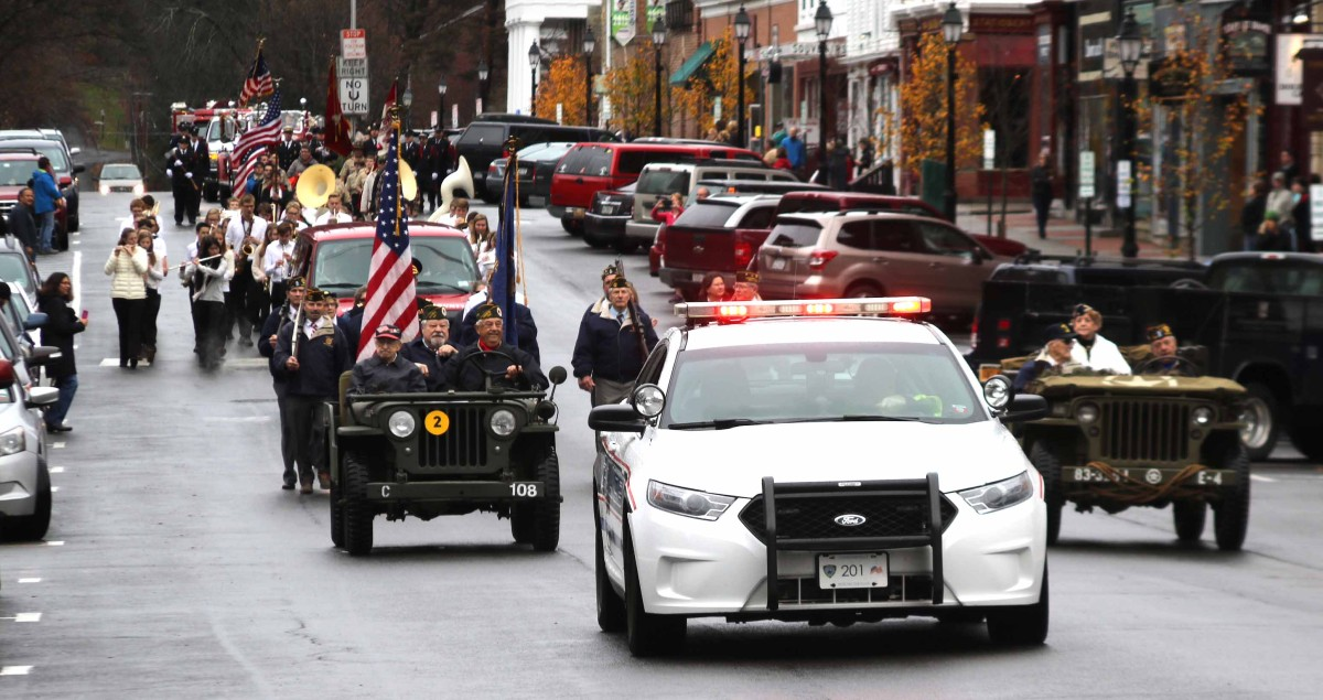 "The Veterans Day Parade heads west on Main Street, Cooperstown, this morning from the Vets' Club enroute to the ""doughboy"" statue. Veterans particularly honored were Jack McGrath, left Jeep, and Joan Clark, right Jeep."