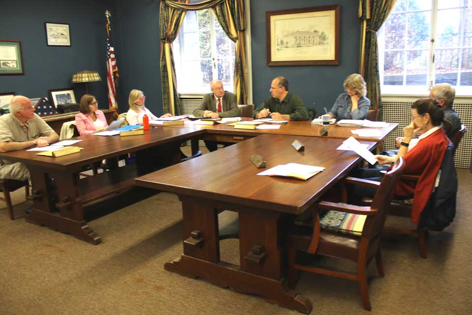 "The Cooperstown Village Board may delay expanding paid parking or seeking the state Legislature's approval of residential parking permits until a full parking study is done, according to discussion among the trustees, meeting at this hour, to discuss the permit possibility. Trustee Cindy Falk told her colleagues every consultant her Streets Committee has contacted said ""we would benefit from a parking study."" She questioned seeking legislative approval for a permit plan ""that two years from now we will contradict."" Mayor Jeff Katz, who argued that two-hour parking should be limited to the environs of the Business District, thought perhaps Bassett Hospital and The Otesaga might be asked to share such a study's cost with Village Hall. The only member of the public present was Pete Henrici, retired teacher and baseball merchant. From left are Trustees Jim Dean, Falk and Ellen Tillapaugh, Village Attorney Martin Tillapaugh, Katz, Village Clerk Teri Barown, and Trustees Lou Allstadt and Joan Nicols. Bruce Maxson was absent. (Jim Kevlin/AllOTSEGO.com)"