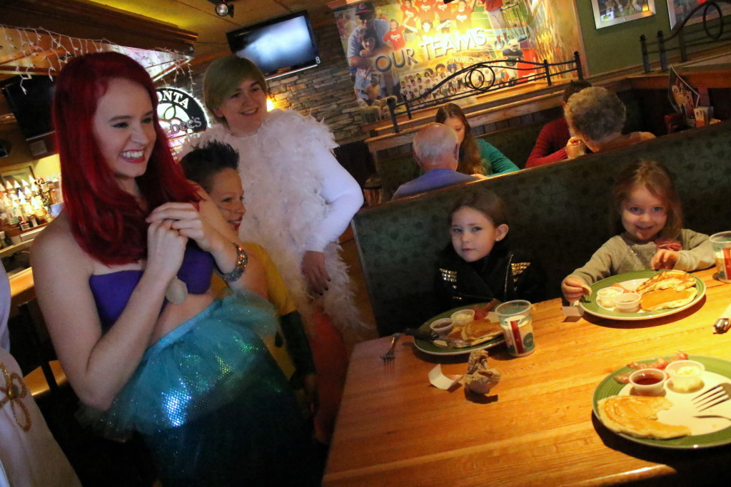 Oneonta sisters Emily and Sarah Ramsey, left, get a visit from Ariel, (Evelyn Iversen), Flounder (David Gouldin) and Scuttle (Quinn Kelley) at the Orpheus Theatre's The Little Mermaid Character Breakfast at Applebee's this morning. The performance will be held on Dec 18-19th at Goodrich Theatre on the SUNY Oneonta campus.(Ian Austin/AllOTSEGO.com)
