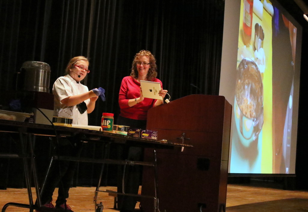 """Julia Rissberger readies for her food demonstration at the OHS auditorium for the middle school, while her mother Rachel projects the proceedings on the big screen for the audience. Julia, who in was a winner of PBS' Healthy Lunchtime Challenge in July. She was preparing an original no bake recepie she calls """"Bird Food"""", made form peanut butter, dried fruit and seeds. Later, she was joined by Chef Jim Perillo from the Otesaga Resort Hotel who shared his carrot hummus recipe. (Ian Austin/AllOTSEGO.com"""
