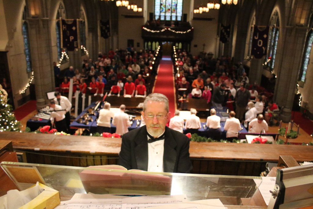 John Jurgensen, director of Music Ministries at FUMC and Dean of the Oneonta chapter of the American Guild of Organists, leads the sanctuary in 'On This Day The Earth Shall Ring' by Arnold B. Sherman at the 42nd annual Community Christmas Carol at First United Methodist this afternoon. In addition to the organ, Jurgensen lead several soloists and bell choirs in holiday favorites new and old. (Ian Austin/ AllOTSEGO.com)