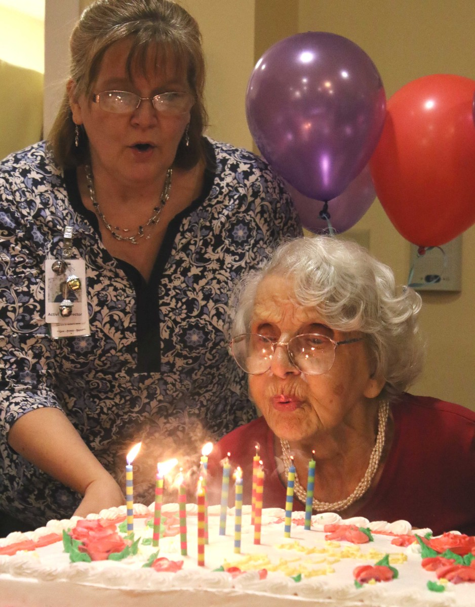 """Focus Rehabilitation resident Asa Skaloud, a Czechoslovakia native who spent her career as a seamstress and hatmaker in Jackson Heights, Queens, blows out the candles on her 100th birthday cake this afternoon in the center's Mountainview neighborhood. Fellow residents sang """"Happy Birthday"""" and congratulated her on the milestone. Activities Director Amy Rose cheers Asa on. (Jim Kevlin/AllOTSEGO.com)"""