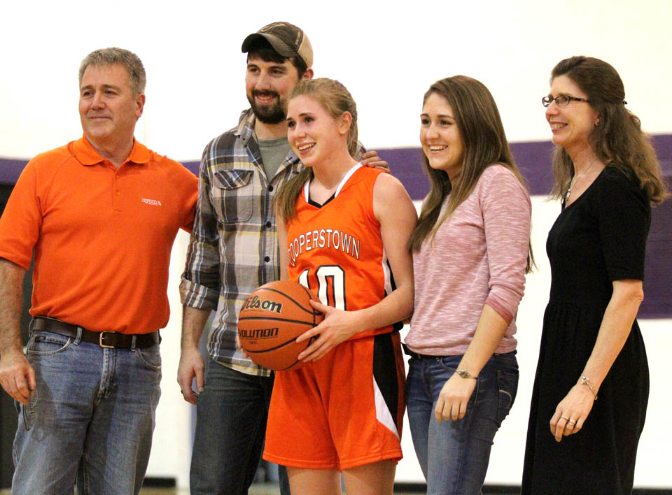 Cooperstown senior guard Liz Millea was joined on the court by her family following her record breaking shot in Milford Tuesday. Millea scored a season high 34 points, and broke Samantha Fox's school career scoring record. The Hawkeyes defeated the Wildcats 50-35 in the non-league game. (Cheryl Clough/AllOTSEGO.com)