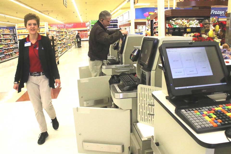 Price Chopper sales clerk Brenda Dewey casts a curious eye at the self-checkout terminals now being installed at Cooperstown's Price Chopper. Paul Somers from company headquarters in Schenectady is on site today, testing out the new equipment. (Jim Kevlin/AllOTSEGO.com)