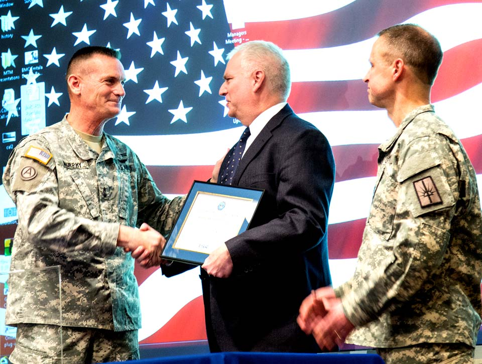 """Maj. Gen. Patrick Murphy, adjutant general of New York State, presents Bassett President & CEO Vance M. Brown with the """"Employer Support of the Guard and Reserve Above and Beyond Award."""" Dr. William LeCates, who has completed three deployments since 2013, nominated Bassett and Brown for the award, which was presented Thursday. """"The support system we have back home when we serve is critically important,"""" Murphy told Vance at the award ceremony. """"All of you are there for our servicemen and women every day making it possible for us to deploy in service to our country. Through your support of Lieutenant Colonel LeCates and others, you have impacted countless lives."""" (Bassett Hospital photo)"""