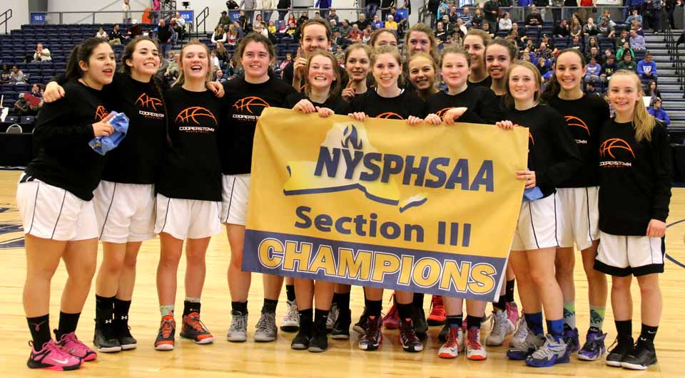 The Cooperstown Hawkeye girls pose with their Section III Class C Championship banner after defeating Syracuse Academy of Science 54-30 in the finals at Onondaga County Community College Sunday afternoon. They will next play Watkins Glen the Section IV Champion next Saturday at Colgate University in the New York State quarter-finals with the winner advancing to the Final Four at Hudson Valley Community College in Troy the following weekend. Cooperstown is the defending New YOrk State Class C Champion. (Brian Horey/AllOTSEGO.com)