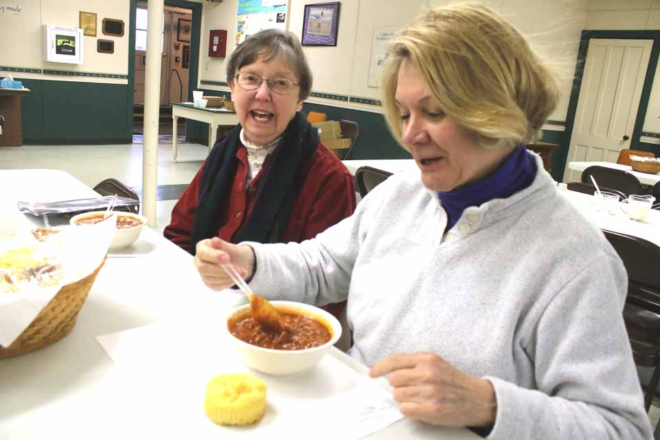 Retired CCS teachers Rena Lull, right, and Dawn Dietz were among the first to partake in today's Soup'r Chili Luncheon at Cooperstown Methodist Church, the traditional kick-off event of the Cooperstown Winter Carnival, underway through Sunday. Attendees include the Rev. Douglas Deer, the church's retired pastor. Servings continue through 2 p.m. (Jim Kevlin/AllOTSEGO.com)