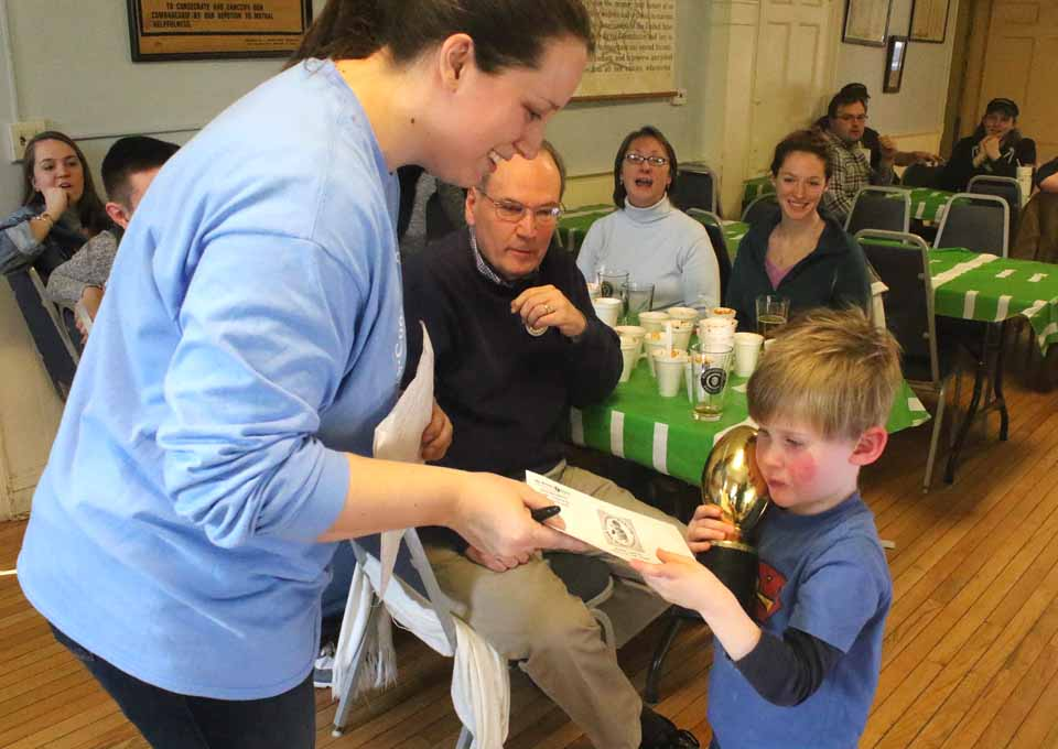 Young Tim Feury claims the $500 check from Winter Carnival Committee chair Marissa Davidson that he won by finding the Carnival Medallion – a golden football – Friday afternoon at Badger Park. For the ninth year, the prize presented at this afternoon's Carnival Closer came from The Freeman's Journal & Hometown Oneonta. Seated behind them are Jim and Teresa Donley and their daughter Dierdre. In photo at right, Carnival Committee member Shirley Tyler announces that Edgar Stevens, a Vets Club member, won the $1,000 raffle. Christine Bell is at right. (AllOTSEGO.com)