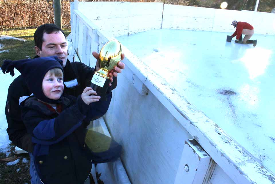 Tim Feury, 2, holds up the 2016 Winter Carnival Medallion – in the form of a golden football – that he found this afternoon tucked against the outside of the east-end backboard at the Badger Park Rink. With him is dad Ted. (JIm Kevlin/AllOTSEGO.com)