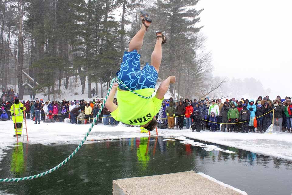 """It's here! The 2016 Goodyear Lake Polar Bear Jump begins at 12:30 Saturday (registration is 9-11:30 a.m.) on the east side of the Town of Milford lake. Jump co-organizer Jamie Waters (with wife Brenda) reports """"pretty good ice"""" – 9-10 inches – on the plunge site. More than 300 jumpers are already registered, and he estimated the total my near 350. Waters and about 30 organizers were on the surface today, setting in place the hot tubs, two new changing rooms, trailers and other jump-related items. Saturday's festivities will end with the annual banquet at 6 p.m. at the Oneonta Elks. Photos is from last year, showing Victor Erway of Fly Creek doing a somersault into the icy deep. (AllOTSEGO.com file photo) LEARN ABOUT THIS YEAR'S JUMP BENEFICIARIES"""