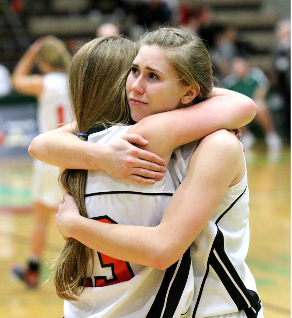 Liz Millea and chidlhood friend and teammate Jen Flynn share a hug as Jen fouls out with just 30 seconds left in Cooperstown's 57-44 State semi-final Class C loss to Pine Pliains at HVCC in Troy.