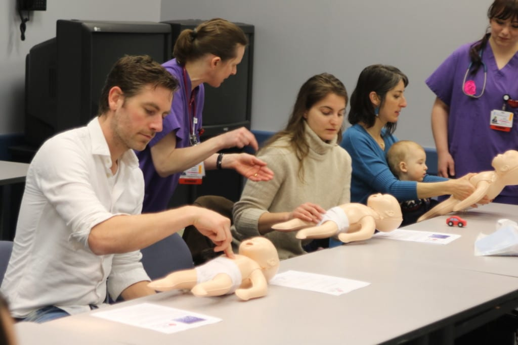 Henryk Revich, Elizabeth Bankus and Diana Cozzins with son Leone, learn the proper way to preform CPR on an infant from ONC Boces nuring students Annabel Doherty, and Sierra Kellerhouse. The class was one of several educational events at the 4th annual Community Baby Shower at the Fox Care Center in Oneonta this afternoon. Also offered were car seat safety courses, human service providers, and many tables and booths from maternal health providers and child development specialists from the area. (Ian Austin/AllOTSEGO.com)