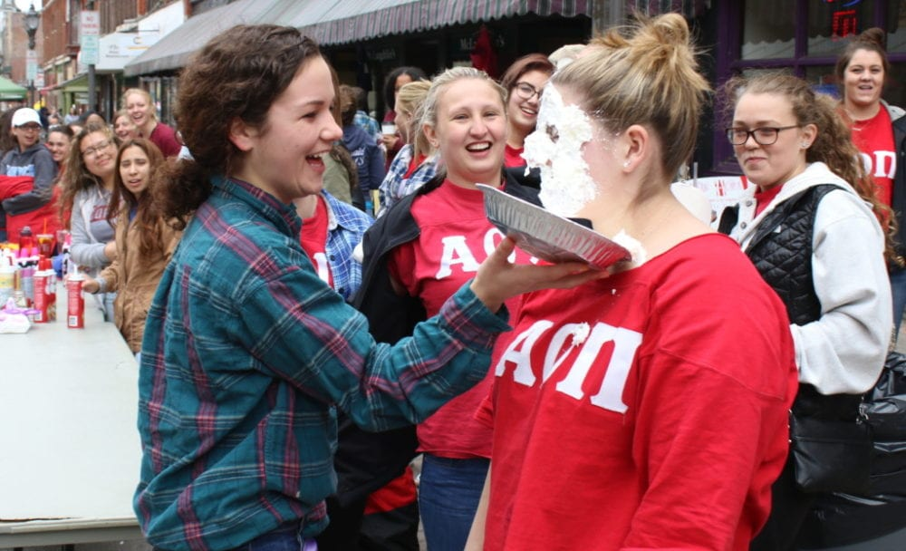 "Gina Profetto, left, plants a tin full of whip cream in the face of Rachael Utegg, whose sorority, Alpha Omega Pi, was hosting ""Pie a Pi"" to raise money for juvenile arthritis. Locals and students alike filled downtown for the annual OH-Fest Carnival which featured food, games, live music and vendors. The festivities continue tonight in Neawah Park with headliner Kid Ink. (Ian Austin/AllOTSEGO.com)"