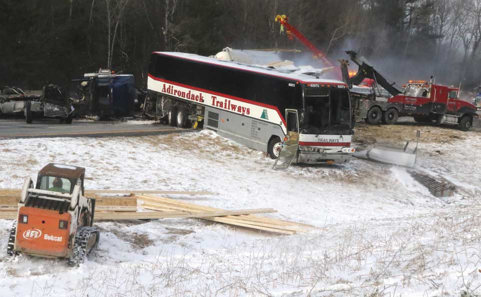 By later afternoon, this was the scene: the Trailways bus, and three rigs sandwiched behind it. Six tow trucks from as far away as the Capitol District were painstakingly removing the wreckage. (Jim Kevlin/AllOTSEGO.com)