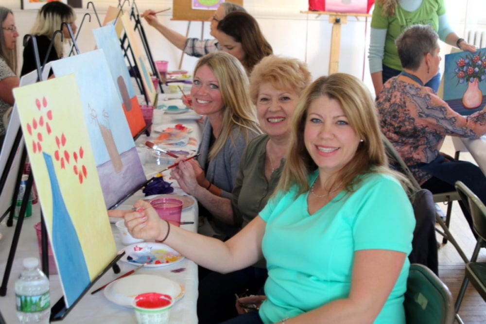 Mothers and daughters enjoyed an afternoon of art and wine at CANO's first annual Paint and Sip. With wine from Dietz and Wall Wines and the guidance of Annie Kuhn, participants tried their hands at painting a mother's day bouquet in acrylics. Here, Lisa Nunez, Oneonta, front, sister Debbie Iannella, Oneonta, rear, pose with their mother Loretta Costello, Center, who came up to visit from New Jersey, pose with their paintings in progress. (Ian Austin/AllOTSEGO.com)