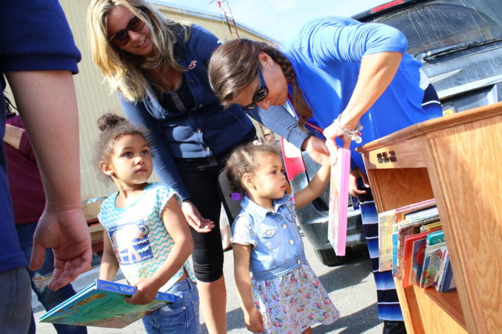 """Rebecca McManus, Center Director of Head Start, right, helps Oneonta sisters Laila Morten and Aaliya Little and their mother Jessica Morten look through their new bookshelf. """"This is so wonderful."""" said Jessica Morten. """"It's such and important thing for families to read to kids and this gives that opportunity to people who may not have that many books."""" The parking lot was a flurry of activity this afternoon Tenfold Plus members and Oneonta Job Corps students handed out over 90 personalized bookshelves to area children. Ten Fold Plus, the originator of the project collected thousands of children's books to stock the shelves, which were created over the winter by Oneonta Job Corps Cement Masons class. """"It's bittersweet."""" said Mauel Moreno, one of the students who built the shelves. """"We've worked on these for three months, and it's sad to see them go. But knowing (the shelves) would be going to kids, that was our motivation. Seeing the faces of the kids and their parents, seeing them loving what we made, it makes me proud I got a chance to do this."""" Oneonta Job Corps Academy director Chris Kuhn looked out over the sea of shelves being carried off, saying """"I'm so happy to see them all go, but a little sad, too. I guess the only thing to beat those post-project blues is to think up something new!"""" (Ian Austin/AllOTSEGO.com"""