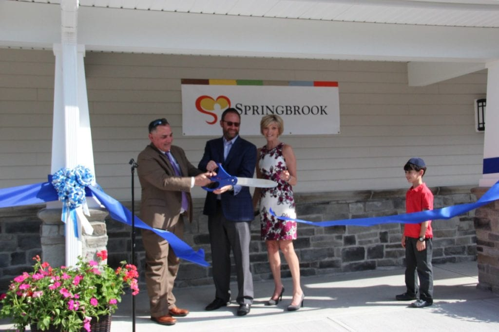 Springbrook Board member Dr. Gerald Pondolfino, Springbrook Parent and Donor Meyer Safdieh, and Springbrook CEO Patricia Kennedy cut the ribbon officially opening the newest home at Springbrook. (Photo Credit: Kira Delanoy)