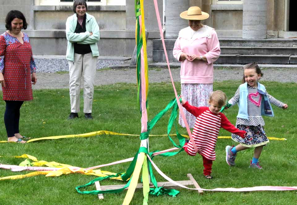 Hundreds of moms (and dads), their children, and just children, young and old, were drawn to Hyde Hall on Otsego Lake today for the National Historic Landmark mansion its increasing popular Mother's Day Weekend festivities.  Above, the Koehn sisters of Oneonta, Adella, 5, and Annika, 3, lace a Maypole, directed by volunteer Mary Margaret Kuhn (in straw hat).  Mom Jenny, left, (as well as brother Alden, 3), helped, as grandmom Aleda Koehn, looked on.  At right, Rick Scheiner of Westford brought mom Barb Schein, of Westford and Newport News,Va., to visit the mansion after attending the Worcester Library benefit luncheon at The Otesaga.  (Jim Kevlin/AllOTSEGO.com)