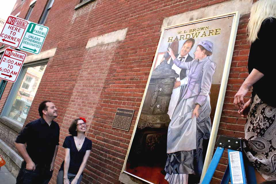 Artist Carol Mandigo, right, this evening unveil the third in a series of five murals planned on the Dietz Street side of the Oneonta History Center, as Libby Cudmore and Ian Austin, depicted in the mural, look on with delight.