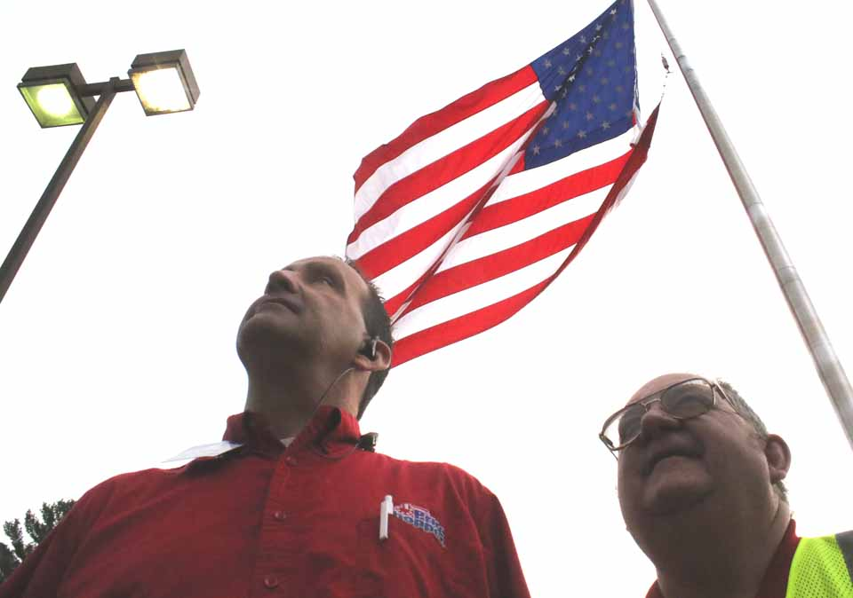 Shoppers, you may have noticed the huge flag raises in the Cooperstown Price Chopper parking lot this week in anticipation of Memorial Day.  Here, assistant manager Jeff Wanly and David Mould are framed by the Stars and Stripes.  (Jim Kevlin/AllOTSEGO.com)