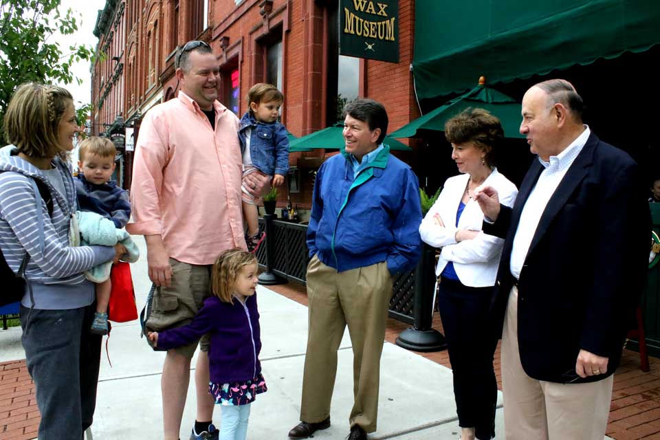 """Republican John Faso, center, who is running to succeed U.S Rep. Chris Gibson in the 19th Congressional District, stops to chat with Reid Nagelschmidt and his family a few minutes ago while campaigning in downtown Coopestown.  With him is wife Mary Frances and, at right, retired assemblyman Tony Casale.  Casale endorsed Faso as """"a true conservative who knows the value of a dollar.""""  Faso will be in Richfield Springs this afternoon meeting with supporters there.  The 19th district primary is Tuesday, June 28, and Faso, a former Assembly minority leader and gubernatorial candidate, will face Andrew Heaney, a businessman from Dutchess County.  Zephyr Teachout and Will Yandik are competing for the Democratic nomination.  (Jim Kevlin/AllOTSEGO.com)"""