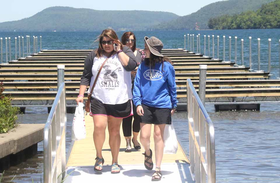 Emma Baldwin, left, and Rebecca Ward, visiting from Iuka, Miss., and, behind them, Kim Brandise of Cooperstown, on her lunch break, try out the just-complete floating docks off Lakefront Park.  (Jim Kevlin/AllOTSEGO.com)