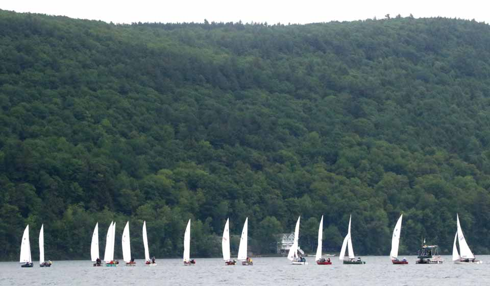 Up Otsego Lake a mile though, Thistle-class national qualifying races got underway off the Otsego Sailing Club about 12:45, delayed from 10 a.m. but not cancelled. At least two crews, Joy Martin and her husband, John Baker, from the Senaca Yacht Club, Geneva, and the three-generation Hudson team from the Saratoga Sailing Club – granddad John, 70, dad Dave, 50, and grandson Peter, early 20s – plan to compete at the 2016 Thistle Nationals at the Eugene Yacht Club in Oregon in late July. (Jim Kevlin/AllOTSEGO.com)