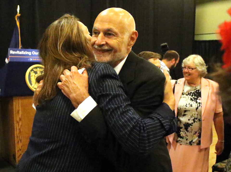 Oneonta Mayor Gary Herzig gets a congratulatory hug from Otsego Now COO Elizabeth Horvath after the announcement that the City of Oneonta will received a $10 million special allocation from Governor Cuomo for downtown revitalization. At right is the city's first lady, Connie Herzig. (Ian Austin/AllOTSEGO.com)