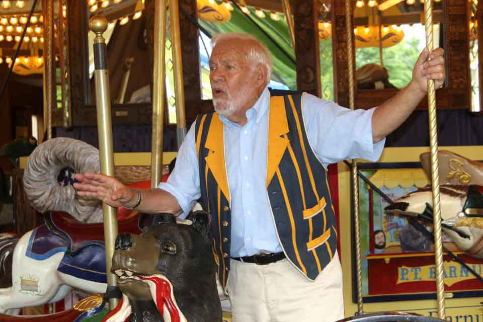 Gerry Holzman tells how the Empire State Carousel started as one man's idea – his – but before the 20-year project was complete, more than 1,000 carvers, quilters and painters had participated in its creation.  Holzman was at The Farmers' Museum today at a ceremony marking the carousel's 10th anniversary in Cooperstown.   Rides on the carousel are free today and Sunday, and Holzman will be giving tours at 11 a.m. and 1, 2, 3 and 4 p.m. tomorrow.  (Jim Kevlin/AllOTSEGO.com)