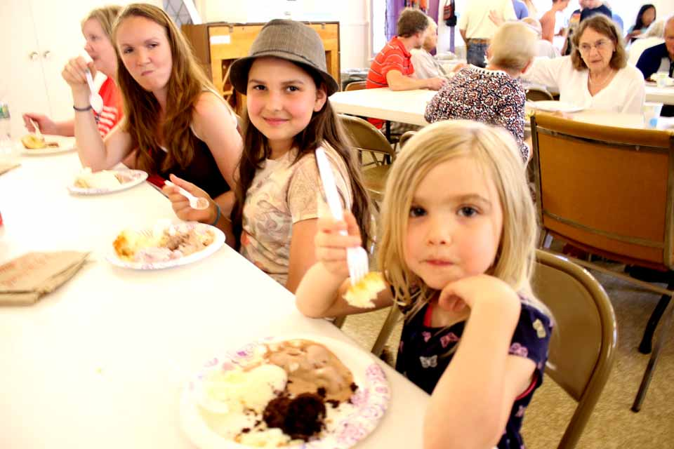 The Moyer girls, from right ,Alice, 5, Madeleine, 12, and mom Emily partake of ice cream and cake at the Cooperstown Presbyterian Church Ice Cream Social, which continues until 8 p.m. at Church and Pioneer, the traditional opener to the Fourth of July Weekend. In this afternoon's downpour, organizers had moved all the tables into the chapel; but, with an hour of sunshine, many of the tables were moved back onto the front lawn. (Jim Kevlin/AllOTSEGO.com)