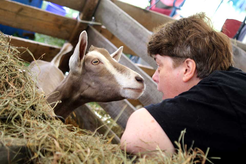 """Kelly Steele, Cooperstown, makes friends with Jean Eugenia the goat. """"I came here for the hugs and kisses!"""" said Steele. I grew up on our families' farm but my father sold our farm after 30 years. I always wanted goats, so I come here!"""""""