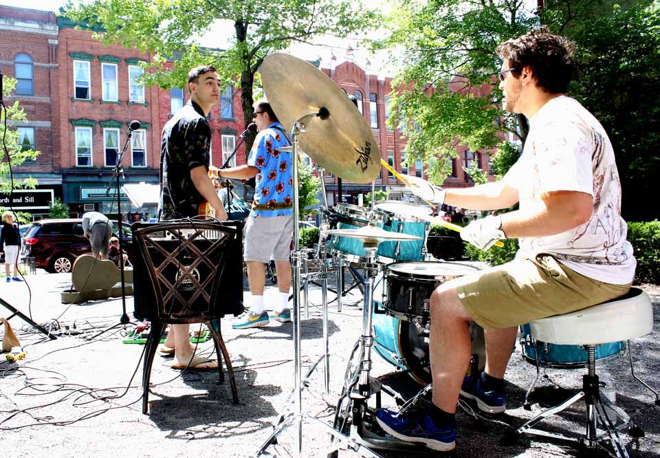 """The rock and roll of the James & Adam Duo today opened the """"Music in the Park"""" series the Cooperstown Chamber of Commerce has organized every Saturday this summer at Pioneer Park in the downtown. Here, James Johnson Jr., left, signals drummer Eamonn Maguire, Cooperstown. In the background is lead singer Adam Coe of Oneonta. Johnson is the son of Jim Johnson, former proprietor of WZOZ radio in Oneonta, and who was watching from the sidelines today. Himself a rocker, the elder Johnson said he and the son had performed the evening before at the B Side Ballroom, Oneonta, owned by his sister, Rebecca Carrington, and her husband Wayne.  (Jim Kevlin/AllOTSEGO.com)"""