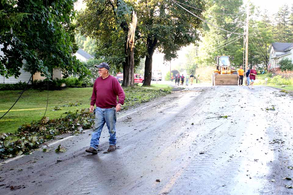Cooperstown firefighter Chip Wright examines cleared trunks and trees branches that closed Route 26 through Toddsville for four hours this afternoon after today's storm split a large tree. The trunk in the background is all that remains. Toddsville was still without power a few minutes ago, but the roadway had been cleared and a NYSEG crew was working to restore power. Also at this hour, it was report that southbound traffic was backed up on Route 28, south of Cooperstown Commons in Hartwick Seminary, but it wasn't immediately clear what the problem is. (Jim Kevlin/AllOTSEGO.com)