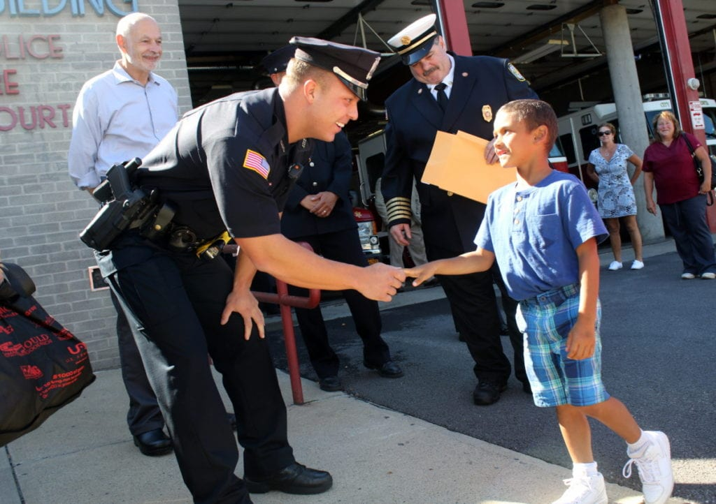 "Oneonta Police Officer Ryan Pondolfino shakes hands with Amari Champen, 5, who was honored by Oneonta Police and Fire for showing bravery in calling 911 after his cousin Devon had a seizure while babysitting him. Pondolfino was one of the officers who responded to the call. ""We've seen 20 year olds with less composure than Amari had,"" he said. Behind them are Mayor Gary Herzig and Fire Chief Patrick Pigeon. Amari was treated to a tour of both stations, as well as certificates and a gift bag for his bravery. (Ian Austin/AllOTSEGO.com)"